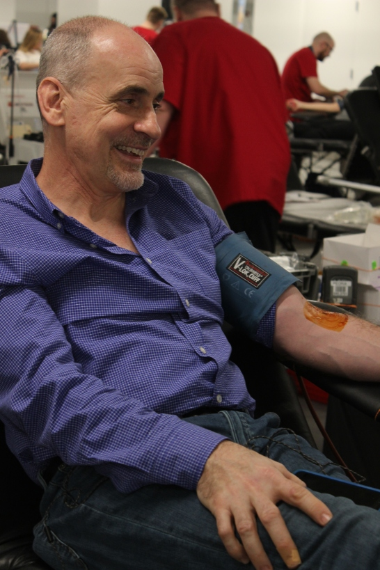 Michael Matura's arm is cleaned with disinfectant as he prepares to donate blood.